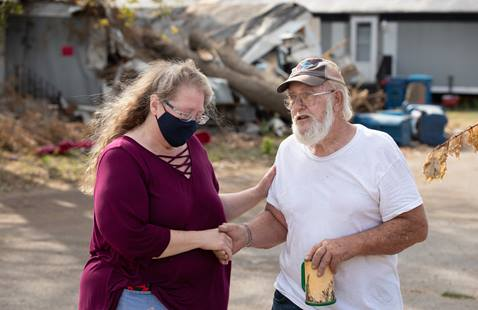 The Rev. Catie Newman prays with John W. Weaver in front of a neighbor's wind-damaged home while a United Methodist volunteer team makes emergency repairs to his roof in Marion, Iowa. Weaver's mobile home was severely damaged during a derecho windstorm Aug. 10. Newman is the disaster response coordinator for the Iowa Conference.