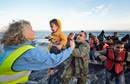 Volunteers carry a child ashore on a beach near Molyvos, on the Greek island of Lesbos, on Oct. 30, 2015, after a group of refugees crossed the Aegean Sea from Turkey in a small overcrowded boat provided by Turkish traffickers to whom the refugees paid huge sums. The refugees were received in Greece by local and international volunteers, then proceeded on their way toward western Europe. File photo by Paul Jeffrey/Life on Earth Pictures.