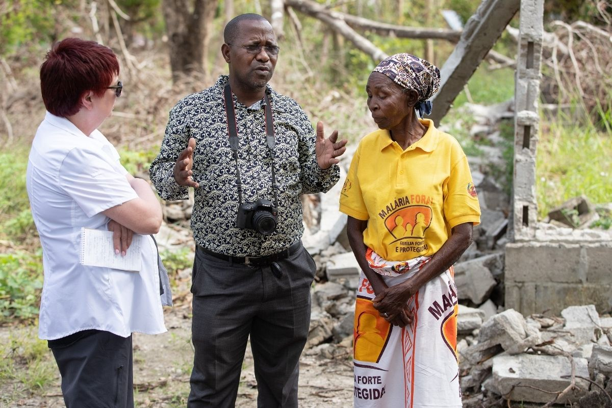 UM News reporters the Rev. João Sambo (center) and Kathy Gilbert (left) visit with a survivor of Cyclone Idai in front of her home in Dondo, Mozambique, which was destroyed by the storm. (Photo by Mike DuBose, UM News)