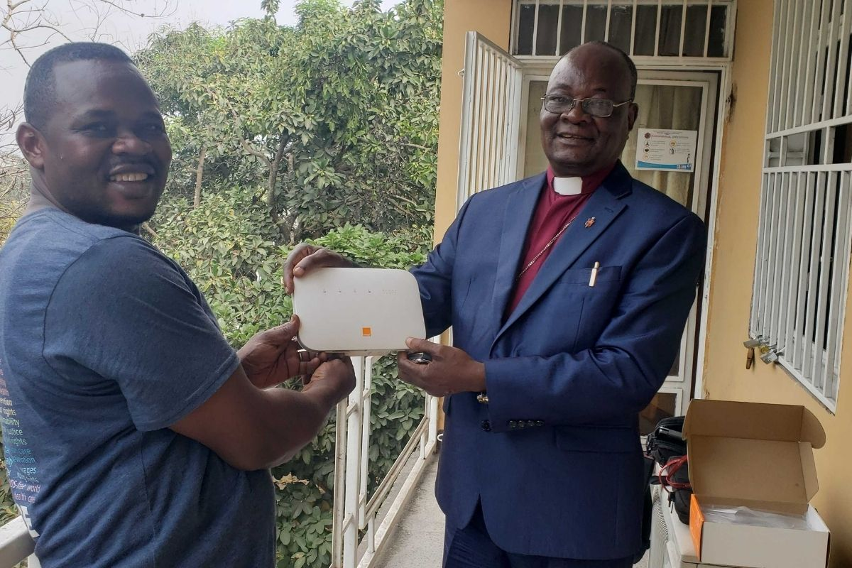 Pierre Omandjela Tangomo (Left), one of the team's field staff and Communicator of the Congo Central Conference, provides the conference's episcopal leader Bishop Gabriel Unda (Right) with equipment during the internet install in East Congo. (Photo courtesy of United Methodist Communications)