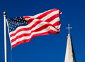 An American flag and church steeple viewed against very clear blue sky. Photo by imdm, iStockphoto.com.
