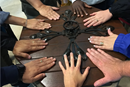 Members of the 2016 Wesley Pilgrimage in England rest their hands on the baptismal font at St. Andrew's church in Epworth where John Wesley was baptized. Photo by the Rev. Anita Mays.