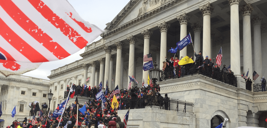 A crowd pressing up the steps towards the Senate Chamber of the Capitol. Photo by Tyler Merbler at Flickr. 2021.