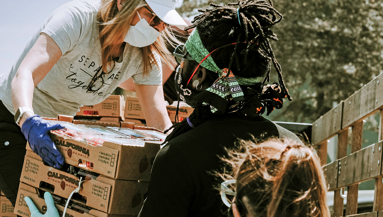Masked volunteers preparing to serve food to the community. Photo by Joel Muniz.