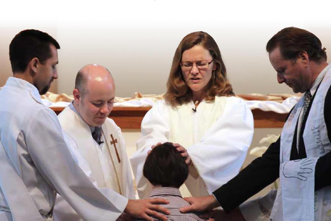 The Rev. Carol Cavin-Dillon (center) prays  for a sixth grader who has just confirmed his  faith at Christ United Methodist Church in  Franklin, Tenn. Photo by Kathleen Barry/UMNS.