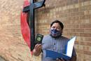Juan Martinez shows off his renewed Mexican passport outside Kingwood United Methodist Church in northeast Houston. The church provided office space and volunteers as a team from the Mexican Consulate in Houston worked to issue and update official documents for Mexicans living in the Houston area and beyond. Photo by Sam Hodges, UM News.