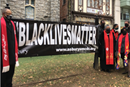 Faith leaders gather in front of Asbury UMC in Washington D.C., to hang a new Black Lives Matter banner after the previous one was torn down and burned by demonstrators on December 12, 2020. Photo by Erik Alsgaard.