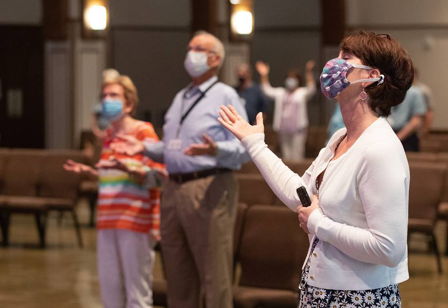 Barbara Layden (front) joins with other parishioners in giving praise during worship at Franklin (Tenn.) First United Methodist Church. The church has adopted safety protocols, including no congregational singing, to help prevent the possible spread of COVID-19. Photo by Mike DuBose, UM News.