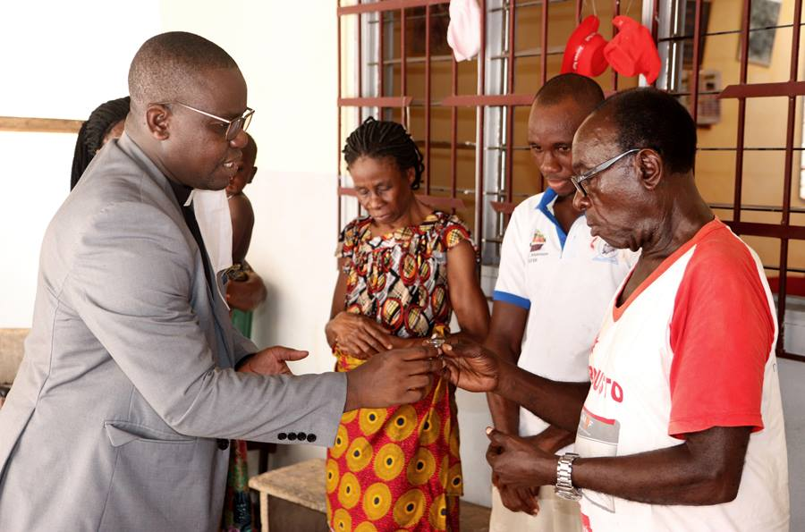 The The Rev. Isaac Broune (left), pastor of Bethel Quartier-Eléphants in Abidjan, Côte d'Ivoire, shares Communion with the Ohouo family (from left, Appolos, Fabrice, Chiadon and Chantal)  during a service in their home. While churches are closed because of the COVID-19 pandemic, members are conducting services at home with resources provided by their pastors. Photo by John Mel, UM News.
