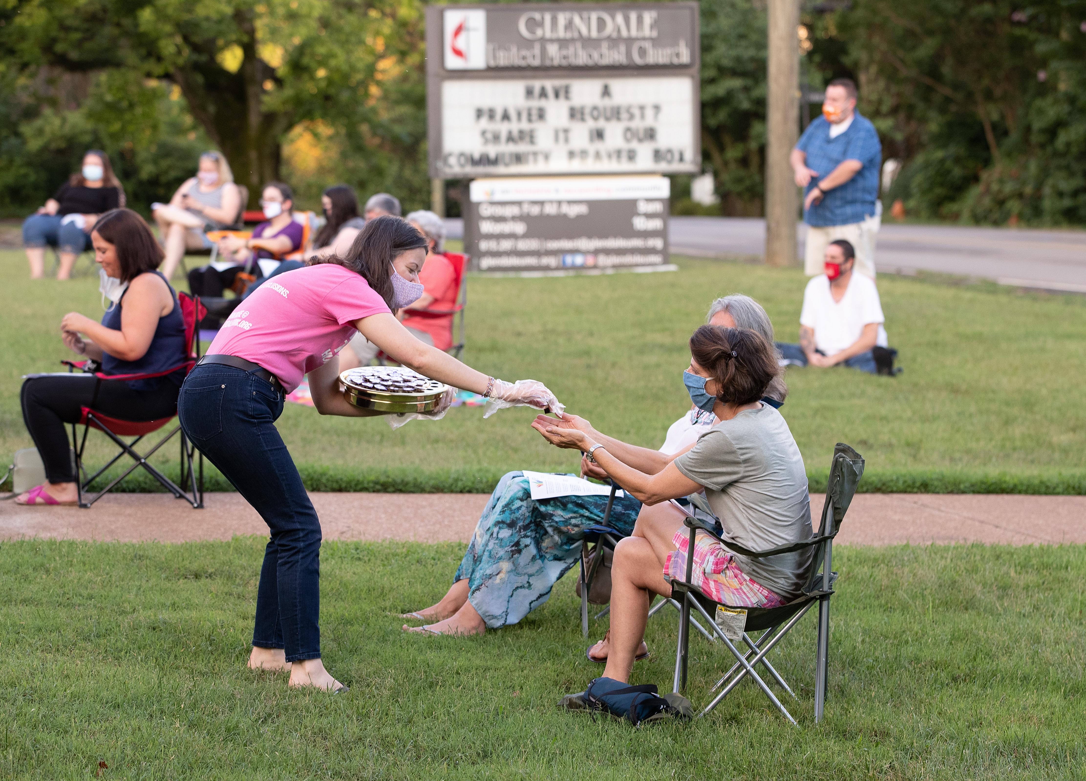 Laura Kreiselmaier serves Holy Communion during an outdoor worship service at Glendale United Methodist Church in Nashville, Tenn., July 26, 2020. UM News.