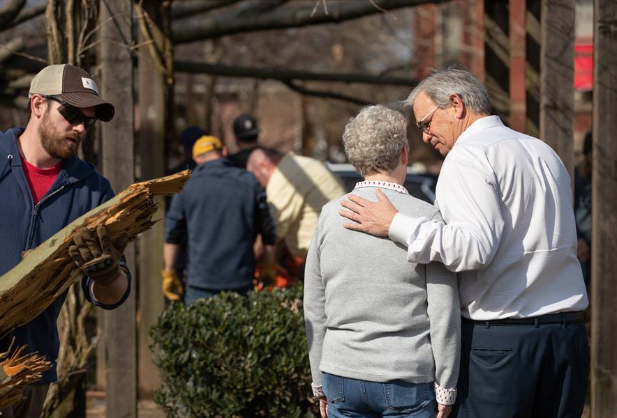 Bishop William McAlilly (right) comforts the Rev. Judi Hoffman in the park outside East End United Methodist Church in Nashville, Tenn., while volunteers clean up debris from a tornado that heavily damaged the church's sanctuary and offices. Photo by Mike DuBose, UM News.