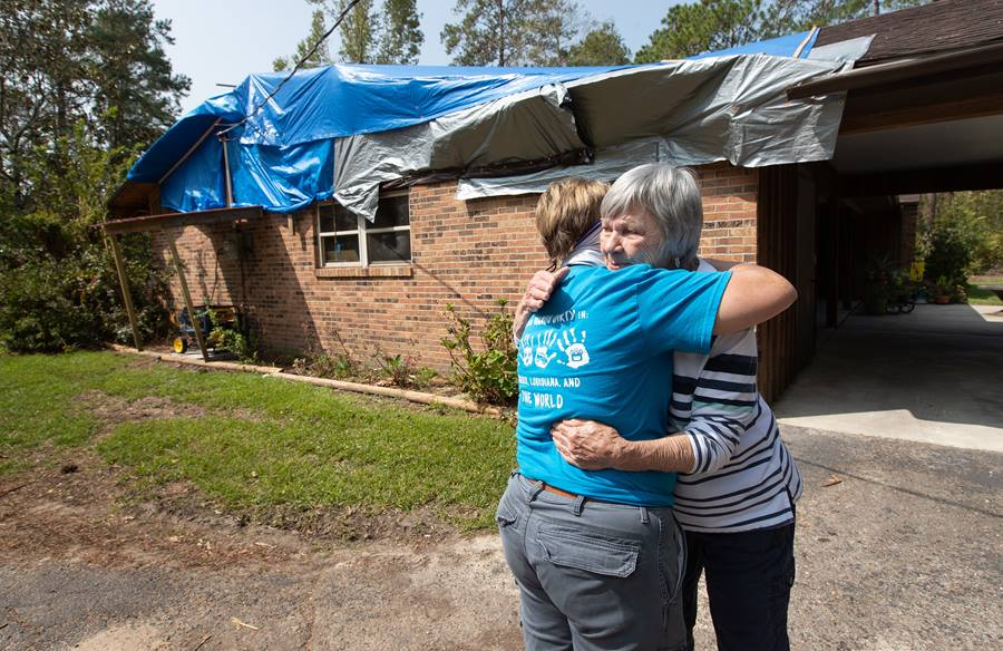 Mary Alice Wisdom (right) hugs her pastor, the Rev. Laraine Waughtal during a visit to Wisdom's home in DeRidder, La., following Hurricane Laura. The hurricane damaged her roof and knocked out electricity. Photo by Mike DuBose, UM News.