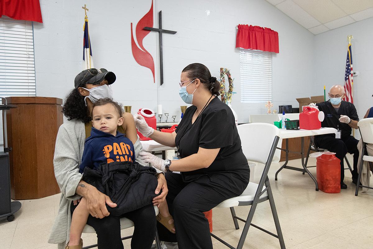 Camisha Henson sostiene a su hijo Welles en su regazo mientras recibe la vacuna COVID-19 de Tabitha England, RN, durante una clínica en la Iglesia Metodista Unida (IMU) San Marcos en Charlotte, Carolina del Norte.