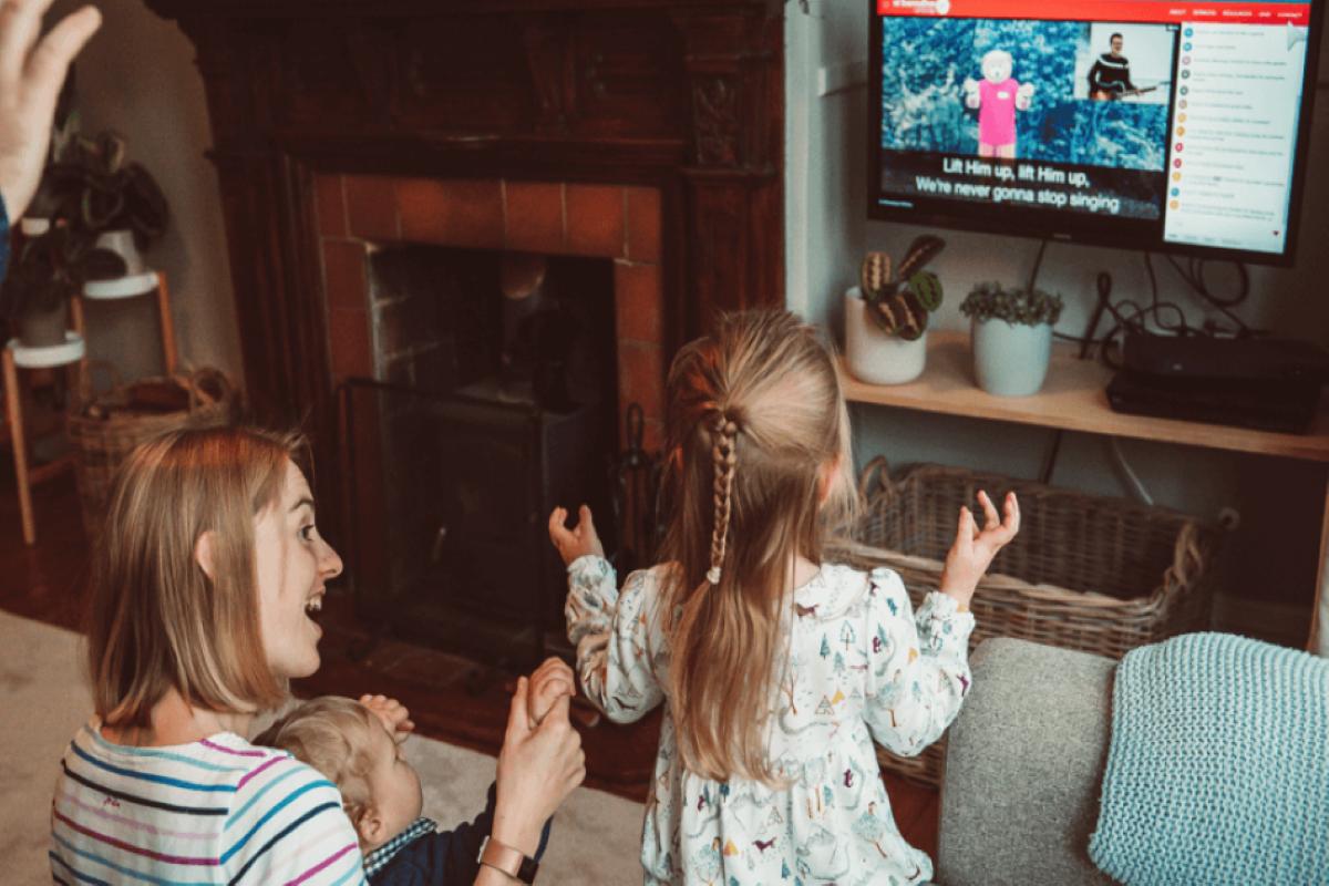 """""""가족이 거실에 모여 박수를 치며 온라인 예배를 드리고 있다. 사진 제공, 루이스 교회 리더십 센터."""""""