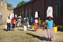 Community members leave with bundles of food and sanitation supplies after a distribution at Murewa Center United Methodist Church outside Harare, Zimbabwe. United Methodist Women, The Nyadire Connection and Harare East District have joined hands to help nearly 800 families struggling with food insecurity during the COVID-19 pandemic. Photo by Kudzai Chingwe, UM News.