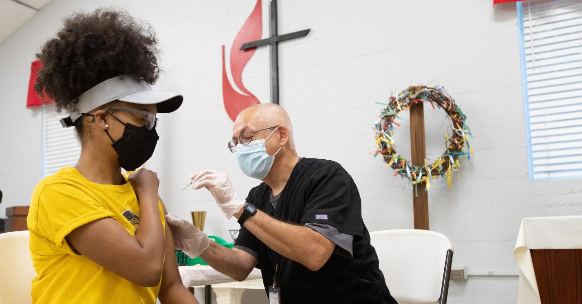 애슐리 핸드는 노스캐롤라이나주 샬럿에 있는 성마가 연합감리교회의 클리닉에서 응급 구조사인 알치 코블로부터 코로나바이러스-19 백신을 맞는다. 사진: 마이크 두보스, 연합감리교뉴스.