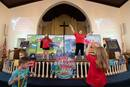 """Children dance in front of the altar rail during vacation Bible school at Connell Memorial United Methodist Church in Goodlettsville, Tenn. The church served as a test site for a new VBS curriculum, """"Food Truck Party,"""" which Cokesbury officially launched on June 30. Photo by Mike DuBose, UM News."""