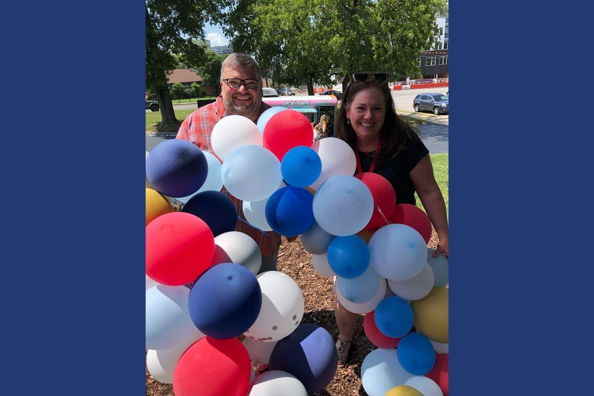 Joe Iovino and Jennifer Rodia took advantage of the festive balloon displays to grab a photo together at the UMCom picnic. (Photo provided by Jennifer Rodia.)