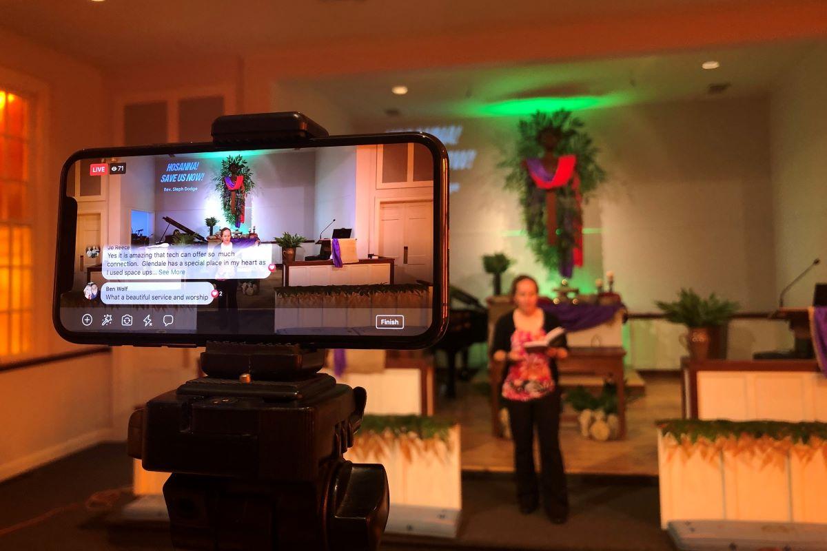 테네시주 내슈빌에 있는 글렌데일 연합감리교회에서 아이폰을 가지고 페이스북 라이브를 통해 온라인 예배를 생중계하고 있다. 2020년 코로나바이러스 전염병으로 인해 많은 교회에서 예배를 드리기 온라인 생중계로 전환했다. 제단에는 담임목사인 스테파니 닷지 목사가 있다. 사진: 스티븐 어데어, 연합감리교회 공보부.