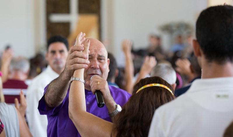 El obispo Ricardo Pereira impone las manos a los congregantes en la Iglesia Metodista de Marianao en La Habana. Foto por Mike DuBose, UMNS.